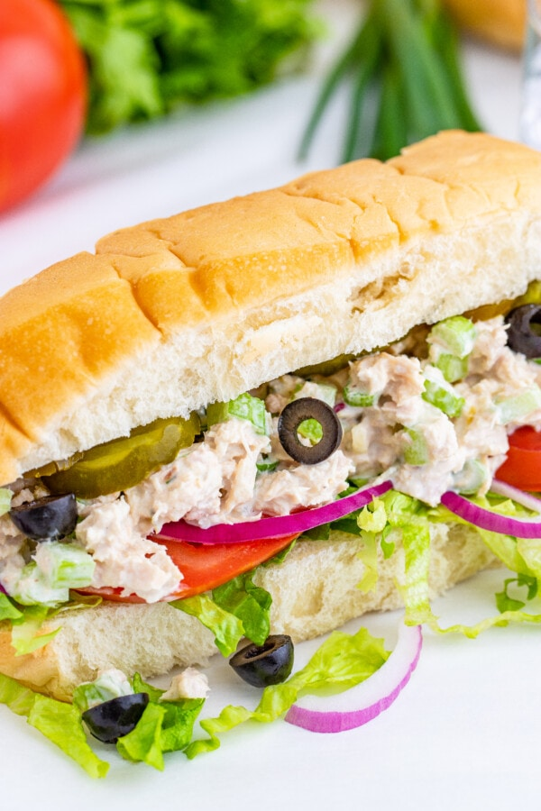 A closeup of a tuna sub with lettuce, tomatoes, olives and pickles