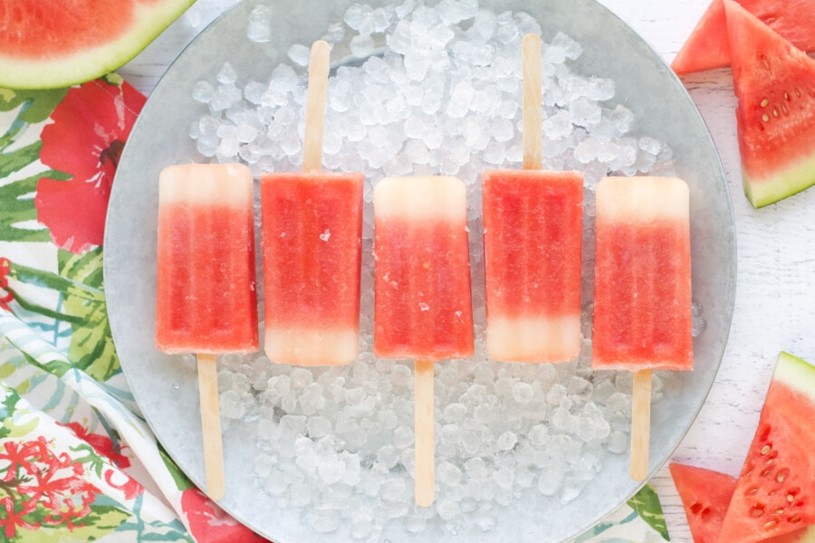 5 popsicles on a bed of ice on a grey platter with fresh watermelon slices.