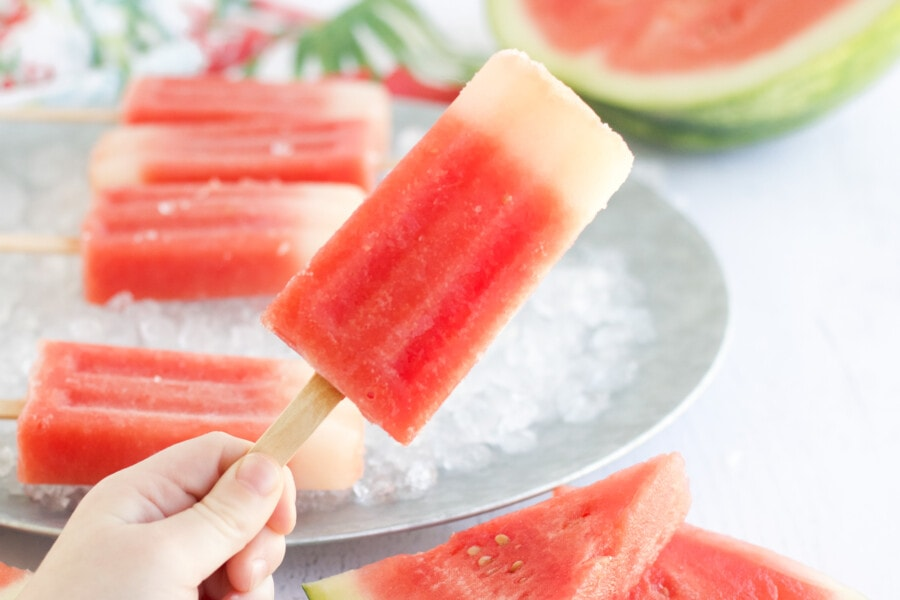 a watermelon popsicle being held in the air with popsicles in background and a fresh watermelon.