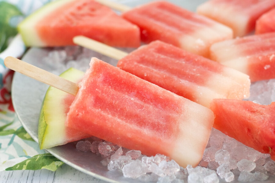 watermelon popsicles closeup on ice with slices of watermelon.
