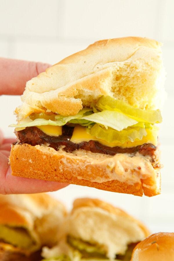 a hand holding an imitation mcdonald's Big Mac slider