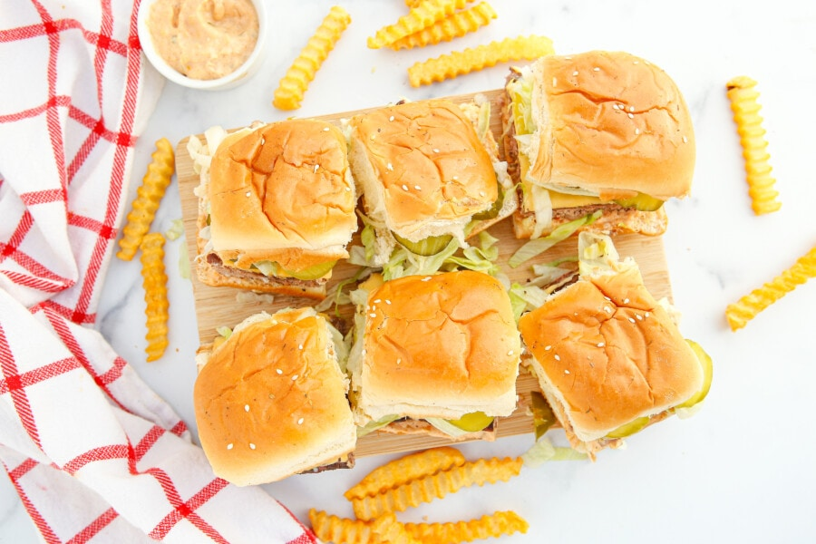 overhead styled shot of six slider burgers with some wavy fries scattered around them