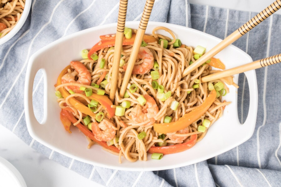 Overhead shot of shrimp lo mein in a serving dish with two sets of wooden chopsticks poised