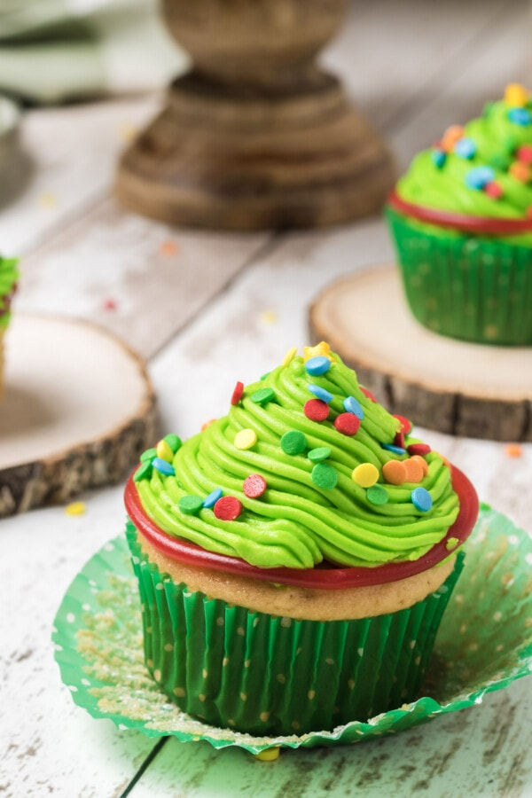 Styled photograph of finished Christmas tree cupcakes with green icing and colorful sprinkles on top looking like Christmas tree lights.