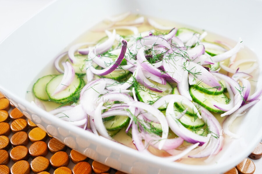 A large square bowl of Grandma's Cucumber Salad on a wooden placemat.