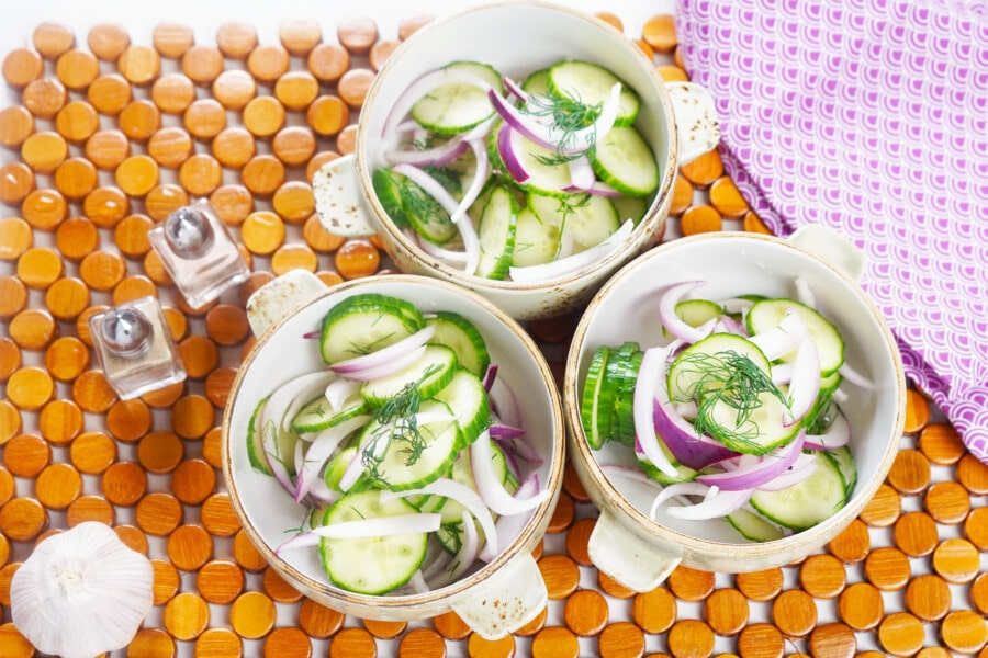 Overhead picture of bowls of vinegar cucumber Salad, salt and pepper shakers and fresh garlic.