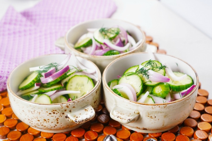 three bowls of Cucumber Salad on a wooden placemat.