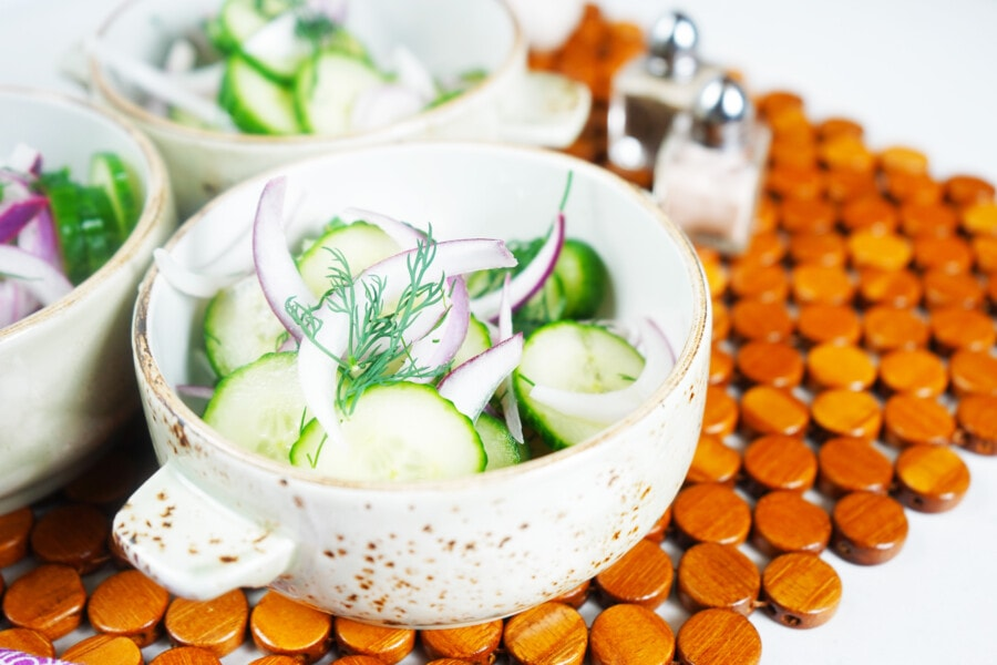 Closeup of Grandma's Cucumber Salad with salt and pepper shakers on a wooden placemat.