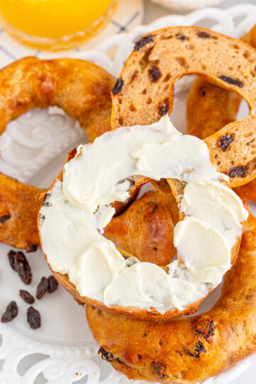 vertical image of air fryer cinnamon rolls on a white plate with one half of a bagel slathered in cream cheese