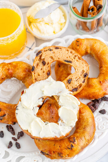 Four cinnamon raisin bagels on a plate that is sprinkled with rasins.