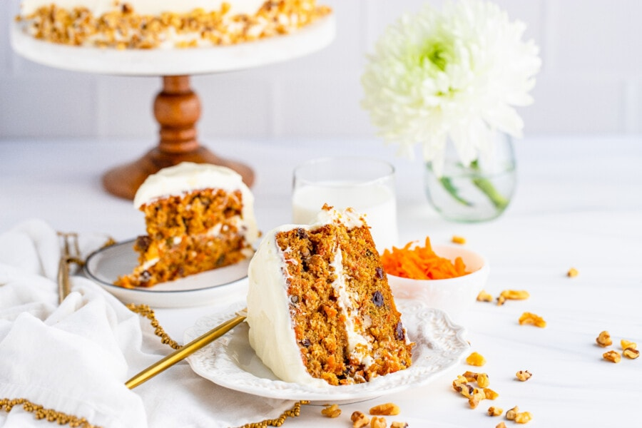 Slice of carrot cake on white plate with another slice of cake on plate in background