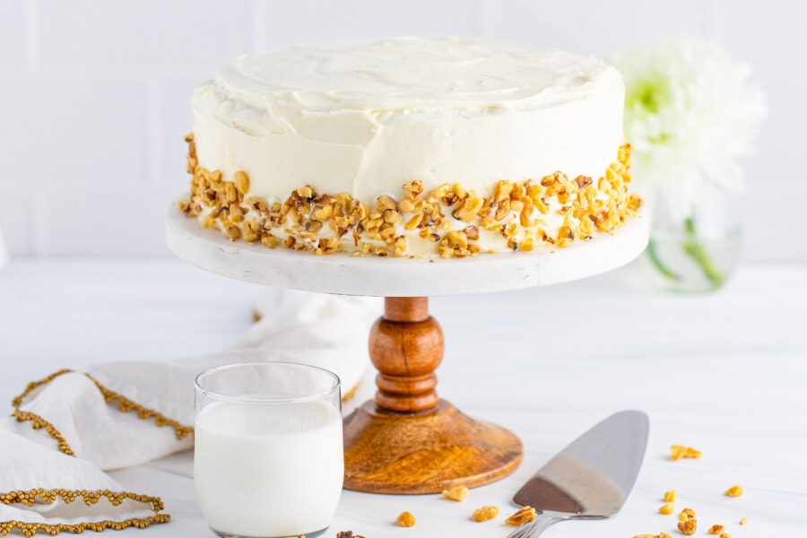 Whole carrot cake on cake stand with glass of milk in front