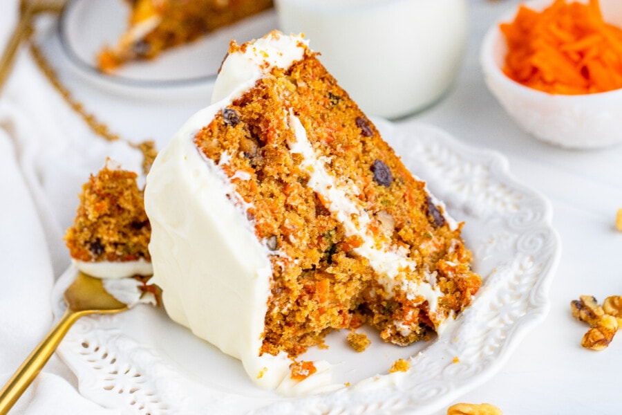 Carrot cake layer cake on white plate with fork