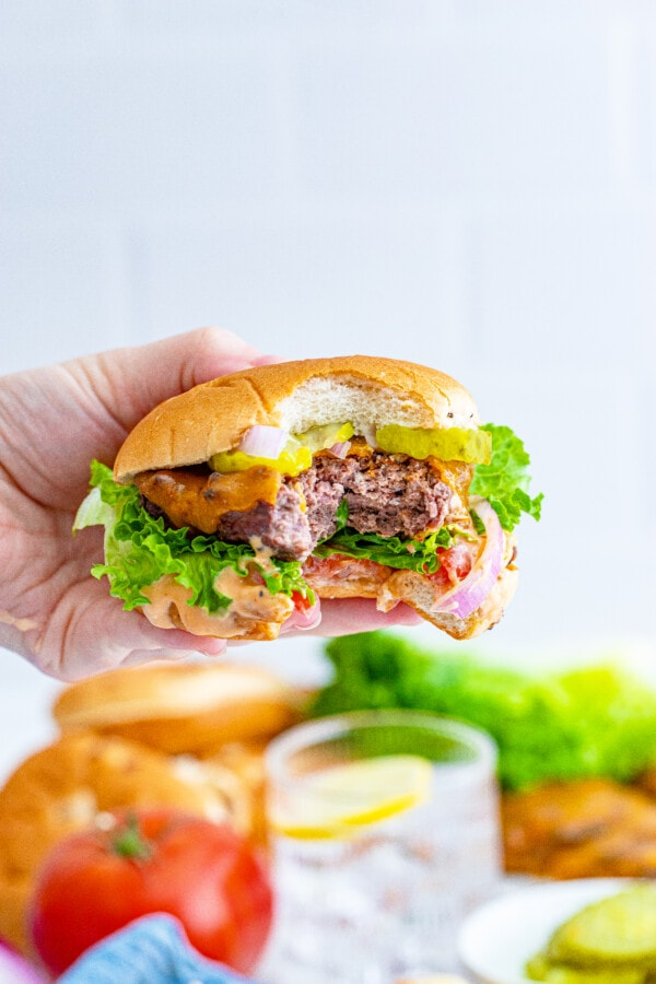 a close up photo of a hand holding a messy venison burger with a bite taken out of it