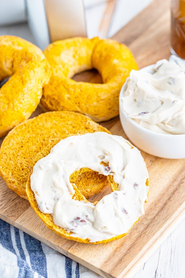 Closeup shot of pumpkin bagels next to cream cheese spread with one pumpkin pie bagel cut in half and topped with cream cheese