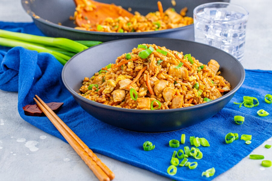 Homemade chicken fried rice in bowl with skillet in background
