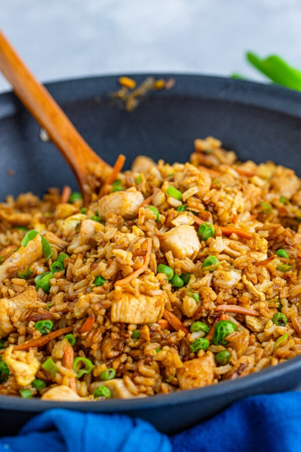 Closeup shot of spoon mixing easy chicken fried rice in skillet