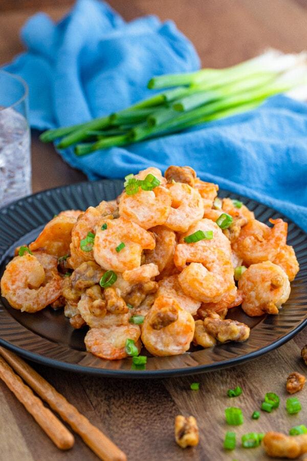 A pile of honey walnut shrimp on a black plate.