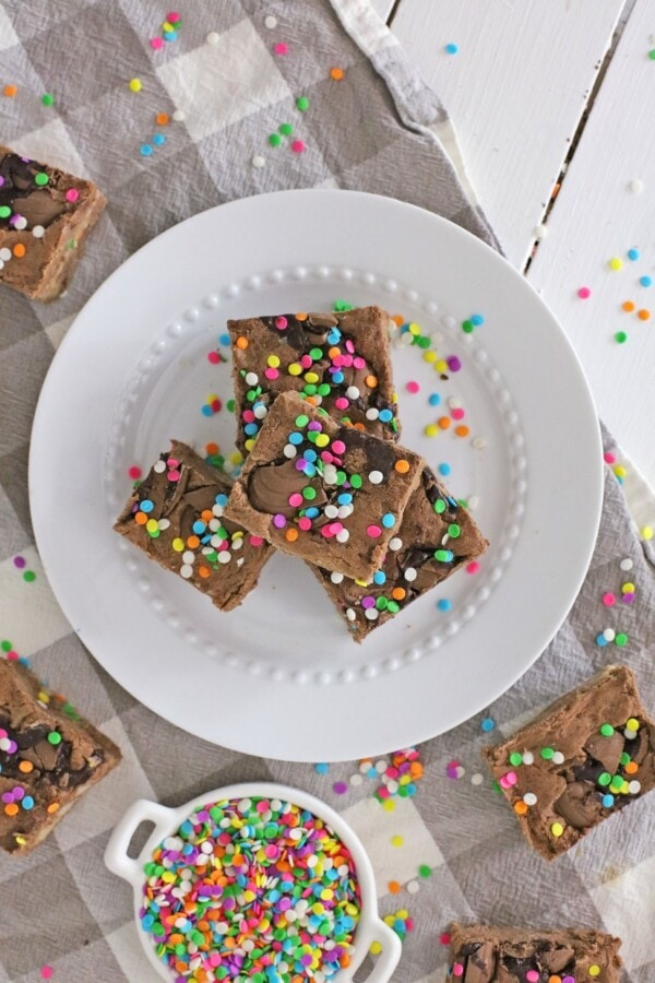 Overhead shot of fudge bars on white plate surrounded by more fudge