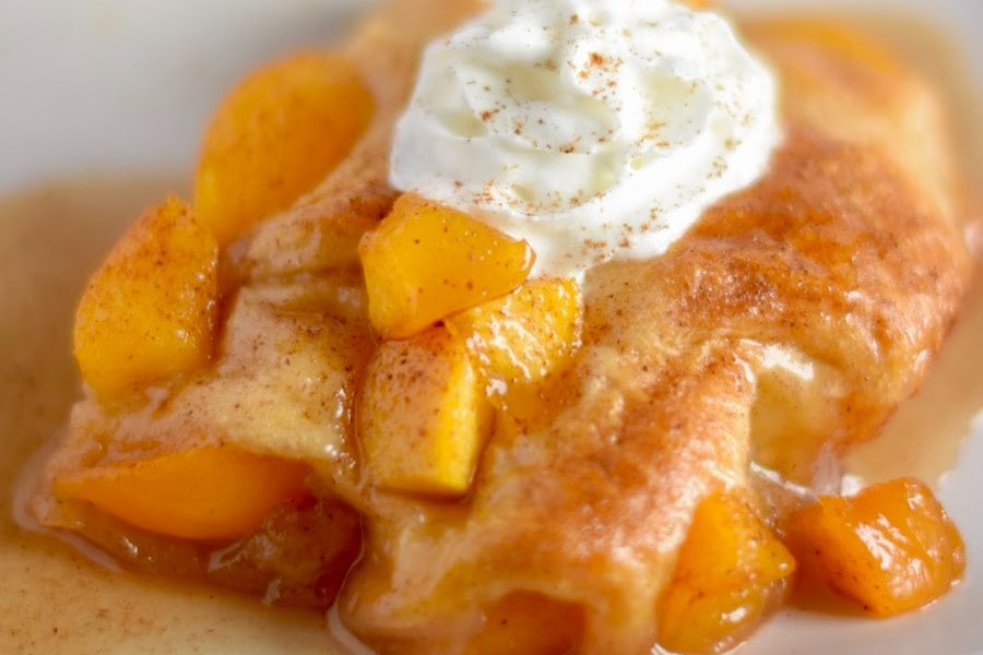 A square of peach cobbler dumplings on a white plate topped with more peaches, cinnamon and whipped cream.