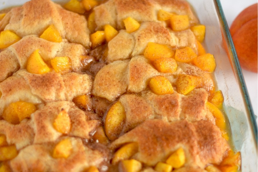 A pan filled with peach cobbler bubbling hot out of the oven.