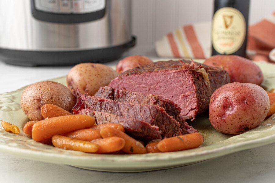 Instant Pot corned beef brisket and vegetables on serving plate with Instant Pot in background