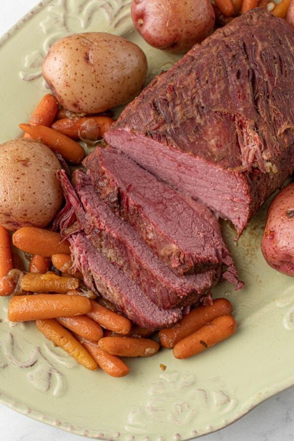 Close up shot of corned beef brisket and vegetables on serving plate