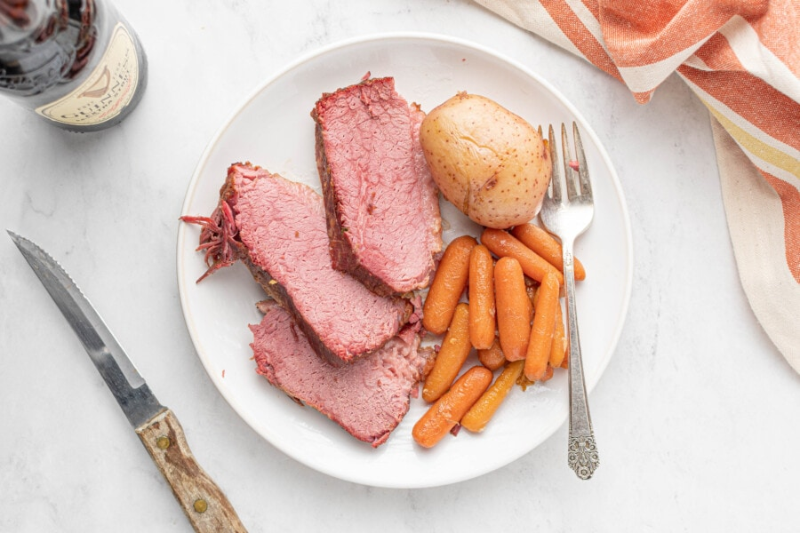 Overhead shot of sliced beef with carrots and potatoes on a white plate